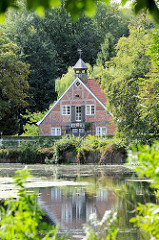 Blick über den Mühlenteich zur ehem. Kupfermühle im Hamburger Stadtteil Wohldorf-Ohlstedt. Das restaurierte Gebäude wurde 1827 errichtet.