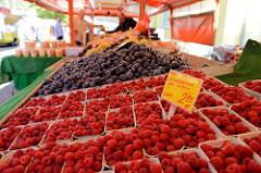Marktstand mit Obst / Obststand auf dem Wochenmarkt in Hamburg Eidelstedt - Elbgaustraße; im Vordergrund frische Himbeeren, dahinter Zwetschgen.