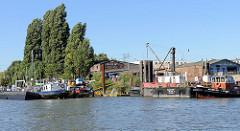 Blick über den Reiherstieg zur Einfahrt in den Grevenhofkanal in Hamburg Steinwerder; Arbeitsboote und Werfgebäude der M. A. Flint Werft.