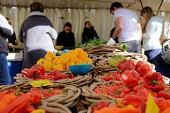 Marktstand mit frischem Gemüse auf dem Wochenmarkt Tibarg im Hamburger Stadtteil Niendorf; verschiedene Paprikasorten liegen in  Weidenkörben.