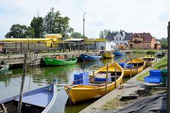 Fischereihafen in in Ziegenort / Trzebież; kleine Holzboote liegen am Kai des Hafenbeckens - im Hintergrund sind Fischernetze zum Trocknen aufgehängt.