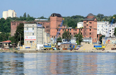 Leerstehendes Backsteingebäude am Hafen von Stettin; Kaianlage mit Kran und Schüttgut.