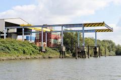 Lagerschuppen mit Krananlage und Liegeplatz im Gewerbegebiet in Hamburg Billbrook; Containerlager am Ufer des Moorfleeter Kanals