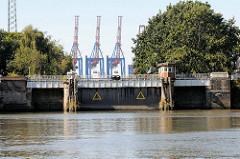 Blick über den Grevenhofkanal zu Grevenhofschleuse in Hamburg Steinwerder; im Hintergrund die Containerkräne vom Waltershofer Hafen / Containerterminal Burchardkai.