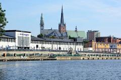 Blick von der Oder  auf das Bahnhofsgebäude / Empfangsgebäude Szczecin Główny. Dahinter historische und moderne Gebäude sowie die St. Jakobi-Kathedrale und dem Turm vom Rektorat der Pommerschen Medizinischen Universität Stettin.