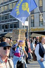 """Protestdemonstration gegen die rechtsgerichtete Kundgebung """"Merkel muss weg"""" in Hamburg. Demonstrationszug mit Fahne und handgeschriebenen Plakat: Menschenrechte statt rechte Menschen""""auf dem Jungfernstieg."""