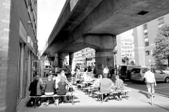Mittagszeit im Hamburger Stadtteil Hammerbrook / City Süd - Restaurant mit Tischen auf dem Gehweg unter dem Bahnviadukt.