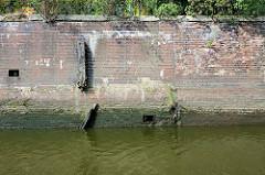 Alte Kaimauer / Brückenfundament der Eisenbahnbrücke über den Tidekanal in Hamburg Billbrook. Ein alter Holz - Streichdalben hat früher die Ziegelwand vor Beschädigung geschützt - jetzt ist er zerbrochen, Wildkraut wächst aus dem vermodertem Holz.