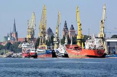 Blick von der Westoder auf die Hafenanlagen von Stettin - Frachtschiffe und Kräne; im Hintergrund die historischen Türme der alten Hansestadt.