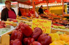 Gemüsestand auf dem Wochenmarkt in Hamburg Eidelstedt -  frische rote und gelbe Paprika liegen in Kisten in der Auslage.
