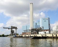 Blick auf das Kraftwerk Tiefstack in Hamburg Billbrook / Billwerder Bucht;  Schuten und ein Binnenschiff  mit Kohle an Bord werden am Kai des Kraftwerks entladen.