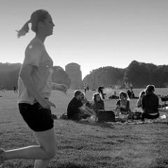 Sommerabend auf der großen Festwiese im Hamburger Stadtpark, junge Leute machen Picknick im Gras - eine Joggerin zieht ihre Runden, im Hintergrund das Winterhuder Planetarium.