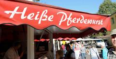 Imbissstand mit Rossspezialitäten auf dem Wochenmarkt in Hamburg Eidelstedt. Aufschrift auf der Plane: heiße Pferdewurst.