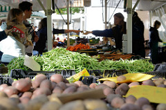 Marktstand mit Obst und Gemüse auf dem Wochenmarkt Tibarg im Hamburger Stadtteil Niendorf; Kisten mit Kartoffeln, frischen Bohnen und Möhren.
