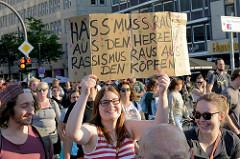 """Protestdemonstration gegen die rechtsgerichtete Kundgebung """"Merkel muss weg"""" """" in Hamburg. Handgeschriebenes Plakat: Hass muss raus aus den Herzen, Rassismus raus aus den Köpfen."""