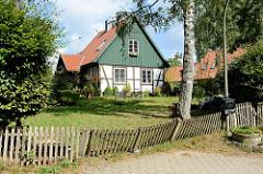 Einzelhäuser / Landarbeiterhäuser an der Herrenhausallee im Hamburger Stadtteil Wohldorf-Ohlstedt; Fachwerk mit Holzgiebel - schiefer Holzzaun.