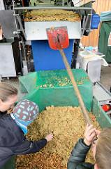 Eine mobile Apfelsaft Pressmaschine / Mosterei wird auf dem Apfel- und Kartoffelfest  vom Gut Wulksfelde den Besuchern vorgeführt; Kinder können die Äpfel auf ein Förderband legen - andere Schaufeln die Apfelreste in einen Bottich.