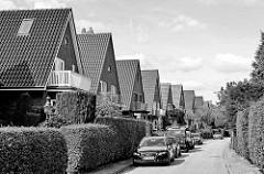 Einfamilienhäuser / Einzelhäuser mit Satteldach in der Gartenstadt von Hamburg Alsterdorf. Frisch geschnittene Hecken Grenzen die Grundstücke ab, Autos parken vor den Häusern.