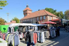 Marktstand mit Kleidung auf dem Wochenmarkt in Hamburg Alsterdorf - im Hintergrund das historische Küchengebäude der Alsterdorfer Anstalten, das unter Denkmalschutz steht.