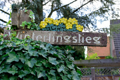 Straßenschild Winterlingstieg - Holzschild geschnitzt in der Gartenstadt von Hamburg Alsterdorf.