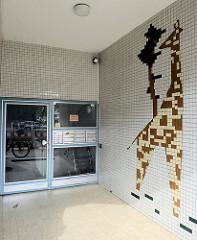 Eingangsdekoration eines Wohnhauses in Hamburg Lurup; Baustil der 1960er Jahre,  Kachelmosaik - Giraffe mit Baum.