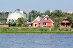 Wochenendhäuser am Ufer der Westoder bei Stettin, daneben Kugeltanks eines Klärwerks.