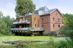 Rückseite vom alten Mühlengebäude am Mühlenteich der Ammersbek im Hamburger Stadtteil Wohldorf-Ohlstedt. Das Gebäude wurde zu Wohnzwecken umgebaut.