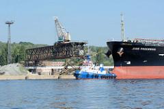 Hafenanlage in Stettin, Kran auf einem Laufgerüst; der Frachter Jose Progress wird von einem FairPlay-Schlepper für die Ausfahrt vorbereitet.
