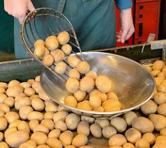 Kartoffelstand auf dem Wochenmarkt in Hamburg Duvenstedt - Kartoffelschaufel und Waagschale.