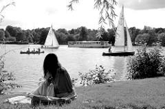 Ufer der Außenalster an der Bellevue in Hamburg Winterhude; ein Mädchen sitzt im Gras und blickt auf die unterschiedlichen Boote, die auf der Alster fahren.