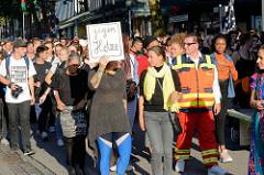 """Protestdemonstration gegen die rechtsgerichtete Kundgebung """"Merkel muss weg"""" in Hamburg. Demonstrationszug mit handgeschriebenen Plakat: Gegen Hetze."""