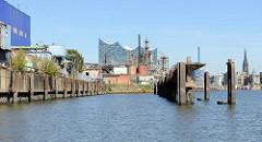 Blick über den Grenzkanal / Steinwerder Hafen zu Kaimauern und Industrieanlagen in Hamburg Steinwerder - im Hintergrund das Gebäude der Elbphilharmonie.