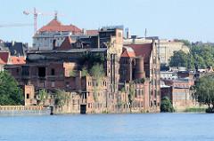 Historische Hafenarchitektur, verfallene Backsteingebäude - Fabrik Anlagen mit abgetragenem Schornstein an der Oder im Hafen Stettin.