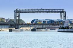 Drehbrücke / Eisenbahnbrücke mit Versorgungsleitungen an der Westoder in Stettin, ein Zug fährt in die Stadt ein.