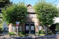 Historische Architektur im Hamburger Stadtteil Nienstedten - denkmalgeschütztes, reetgedecktes Wohnwirtschaftsgebäude / Fachhallenhaus am Nienstedtener Marktplatz.