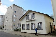 Historisches Wohnhaus in der Lindenstraße von Pinneberg, einstöckiger Satteldachbau - errichtet um 1900. Das Gebäude steht als Kulturdenkmal der Stadt unter Denkmalschutz. Dahinter moderne Neubauten / Wohnblocks.