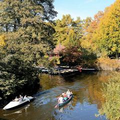 Herbst im Stadtpark von Hamburg Winterhude, ein Ruderboot / Tretboot an der Einfahrt zum Stadtparksee, dahinter die Liebesinsel mit Bootsverleih.