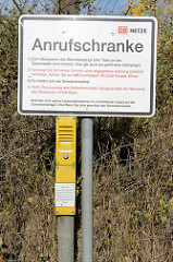 Hinweisschild für eine sogenannte Anrufschranke an der Bahnlinie Hamburg Lübeck beim Naturschutzgebiet Höltigbaum; per Rufknopf wird eine Schrankenöffnung angefordert. Ansonsten ist der Bahnübergang immer geschlossen.