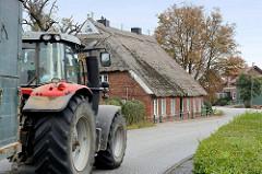 Landwirtschaftliche Verkehr mit Trecker und Anhänger auf dem Ochsenwerder Norderdeich in Hamburg Ochsenwerder; direkt am Fahrbahnrand steht ein altes reetgedecktes Wohnhaus.