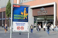 Informationsschild vom Bezirksamt Hamburg Wandsbek für den Wochenmarkt Bramfeld - im Hintergrund der Eingang zur Marktplatz Galerie.