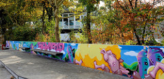 Marktplatz im im Hamburger Stadtteil Bramfeld, buntes Graffiti an einer  Mauer, im Hintergrund das Haus der Jugend.