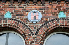 Baudenkmal am Tatenberger Deich im Hamburger Stadtteil Tatenberg, denkmalgeschütztes  Backsteingebäude - ehemalige Schule aus dem späten 19. Jahrhundert - Hamburg Wappen an der Hausfassade.