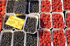 Wochenmarkt auf dem Burchardplatz im Kontorhausviertel in dem Hamburger Stadtteil Altstadt. Marktstand mit frischem Obst - Pappschalen mit Heidelbeeren / Blaubeeren und Himbeeren.