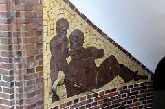 Mosaikendekor im Treppenhaus eines dreigeschossiges Wohn- und Geschäftsgebäude aus Backstein mit Attikageschoss in der Bahnhofstraße von Pinneberg. Das ehemalige Zinshaus wurde 1928 von Friedrich Strupp erbaut und steht unter Denkmalschutz.