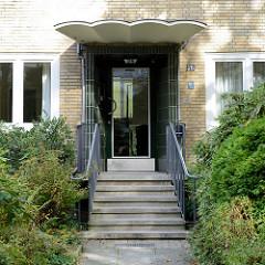 Architektur der 1960er Jahre - Wohnblock im Hamburger Stadtteil Uhlenhorst; gelbe Klinkerfassade, Eingang  mit dunklen Kacheln abgesetzt - tonnenförmiger Regenschutz.   .