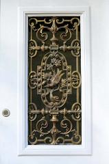Schmiedeeisernes Fenstergitter an der Eingangstür einer Villa in der Bahnhofstraße von Pinneberg. Das 1853 errichtet Doppelhaus steht als Baudenkmal unter Denkmalschutz.
