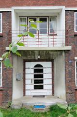 Eingang und Balkon eines Backsteingebäudes  mit Dekorelementen der 1930er Jahre, Architektur im Hamburger Stadtteil Ochsenwerder.