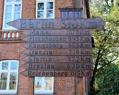 """Handgeschnitzte StädteSchilder mit Hinweis nach Berlin und Städten aus den """"verlorenen deutschen Ostgebieten"""" vor dem Stadtmuseum in Pinneberg."""
