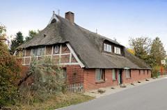 Wohnwirtschaftsgebäude / Fachwerkhaus mit Reetdach in der Heinrich-Osterath-Straße im Hamburger Stadtteil Kirchwerder.