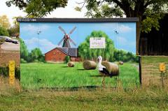 Verteilerkasten einer Energiestation mit Illusionmalerei / Fassadenbild versehen. Weißstorch auf einer Wiese mit Heuballen, dahinter eine Windmühle mit Scheune.